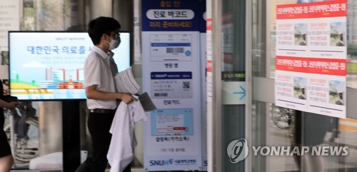 A trainee doctor at Seoul National University Hospital, who earlier held up signs to protest the government's medical reform plan, reenters the hospital after the KMA and parliament reached an agreement. (Yonhap)