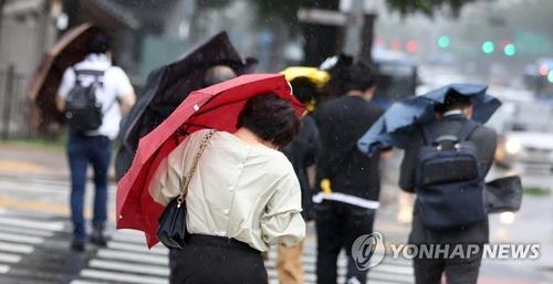 This undated file photo shows citizens crossing a street amid rain and strong wind. (Yonhap)