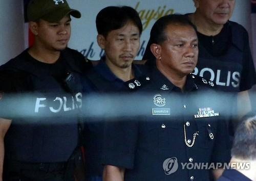 In this file photo from March 3, 2017, Ri Jong-chol (C, rear), wearing a bulletproof vest, heads to a vehicle at a police station in Kuala Lumpur, ahead of his deportation. Ri, 47, was one of the North Korean suspects in the murder of Kim Jong-nam, the half brother of the North's leader Kim Jong-un, who died from what appeared to be a poison attack at the Kuala Lumpur International Airport on Feb. 13, 2017. (Yonhap)