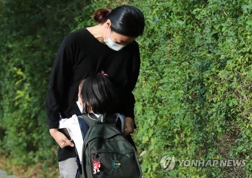 An elementary student hugs her mother before entering a school in Seoul on Sept. 21, 2020. (Yonhap)