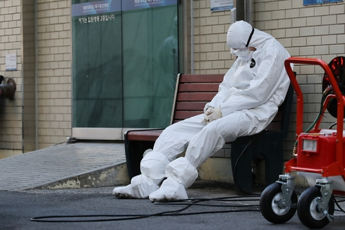 This photo, taken by Lim Hwa-young of South Korean newswire Yonhap News Agency, shows a health worker resting outside a hospital building in the southern city of Daegu. (PHOTO NOT FOR SALE) (Yonhap)