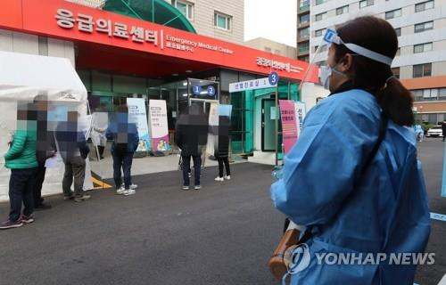A health worker clad in protective gear guides citizens at a makeshift virus testing clinic in Seoul on Nov. 27, 2020. (Yonhap)