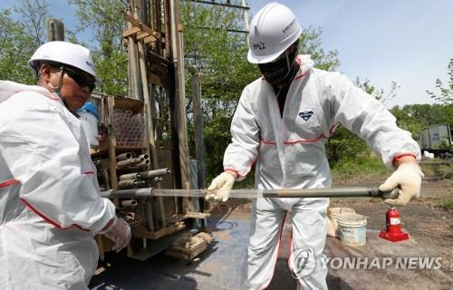 Officials carry out a survey to check the soil contamination level at a former U.S. military base site in Wonju, Gangwon Province, on May 7, 2020. (Yonhap)
