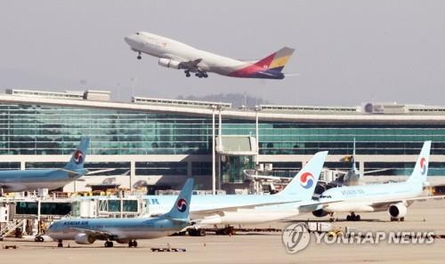 This file photo taken Dec. 1, 2020, shows an Asiana passenger jet taking off from Incheon International Airport with Korean Air planes in the foreground in Incheon, west of Seoul. (Yonhap)