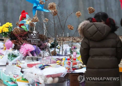 A child pays tribute at the grave site where a 16-month-old girl was buried in Yangpyeong, Gyeonggi Province, on Jan. 4, 2021. (Yonhap)