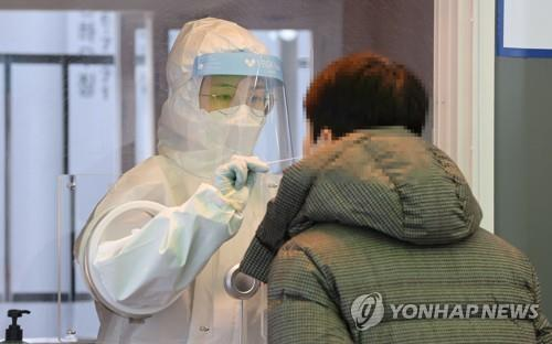 A medical worker collects a swab sample for a coronavirus test at a makeshift COVID-19 screening facility in Seoul on Jan. 23, 2021. (Yonhap)
