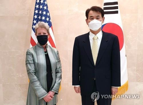The photo provided by the South Korean Embassy in Washington shows Jeong Eun-bo (R), South Korea's top negotiator in defense cost-sharing talks with the United States, and his U.S. counterpart, Donna Welton, posing during their meeting in Washington on March 7, 2021. (Yonhap)