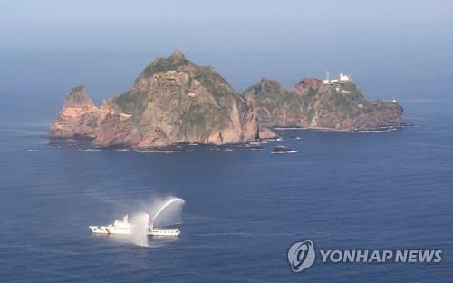 This aerial photo, taken from the Challenger patrol plane of the Korean Coast Guard on Aug. 12, 2020, shows a 3,000-ton patrol boat firing water cannons near South Korea's easternmost islets of Dokdo in the East Sea. (Yonhap)