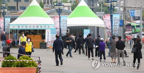 Citizens wait in line to receive virus tests at a makeshift virus testing clinic in Seoul on April 22, 2021. (Yonhap)