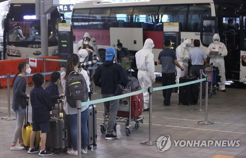 South Korean residents wait to board buses at Incheon airport, west of Seoul, on May 4, 2021, to head for quarantine facilities after arriving from virus-hit India via a special flight operated by Indian air carrier Vistara. (Yonhap)