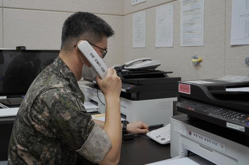 This photo, provided by the defense ministry on July 27, 2021, shows a South Korean service member using the inter-Korean western military communication line. (PHOTO NOT FOR SALE) (Yonhap)