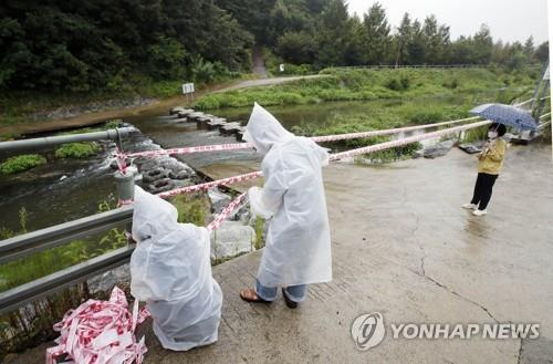 Officials cordon off a road entering a stream in preparation for the arrival of Typhoon Omais, in this photo provided by the Buk Ward office in Gwanju on Aug. 23, 2021. (PHOTO NOT FOR SALE) (Yonhap)