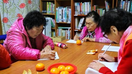 영화 '시인 할매' 스틸컷. 곡성 서봉마을 할머니들이 마을 도서관에서 시를 쓰고 있다. [스톰픽쳐스코리아 제공]