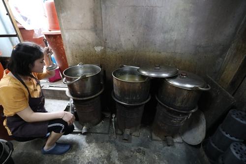 직원이 연탄불 화덕에서 육수 맛을 보고 있다.[사진/성연재 기자]