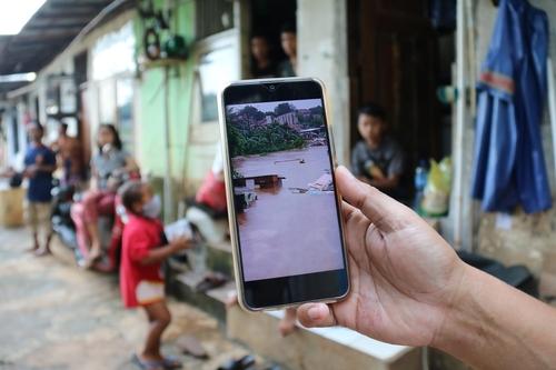 1월 홍수 당시 물에 잠긴 판자촌 사진 보여주는 주민