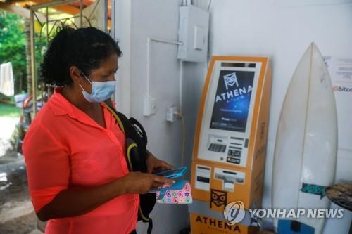 한 여성이 8일(현지시간) 엘살바도르의 한 비트코인 지원 사무실에서 비트코인 거래를 하려 하고 있다. [로이터=연합뉴스]
