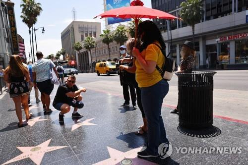 미 캘리포니아 LA의 할리우드 불러바드에서 한 남성이 사진을 찍기 위해 마스크를 벗고 있다. [AFP=연합뉴스 자료사진]