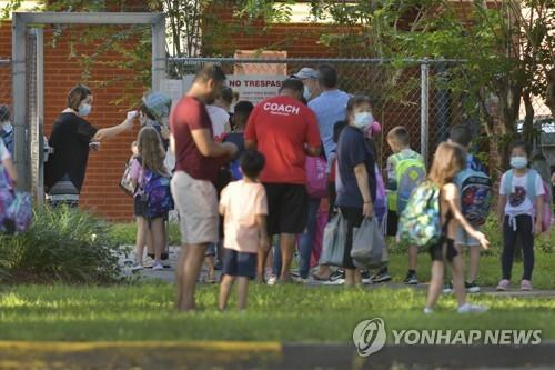 새 학년도 개학일인 10일(현지시간) 미 플로리다주 잭슨빌의 한 초등학교에서 학생들이 학교에 들어가기 전 발열 검사를 받고 있다. [AP=연합뉴스]