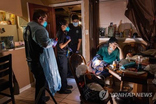 25일(현지시간) 미 텍사스주 휴스턴에서 휴스턴소방서 구급요원들이 코로나19 증상을 보이는 여성을 병원으로 이송할 준비를 하고 있다. [AFP=연합뉴스]