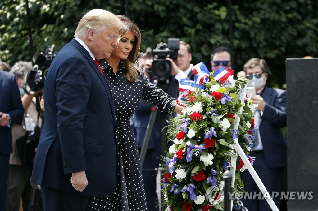 This AP photo shows U.S. President Donald Trump, accompanied by first lady Melania Trump, placing a wreath at the Korean War Veterans Memorial in Washington on June 25, 2020. (Yonhap)