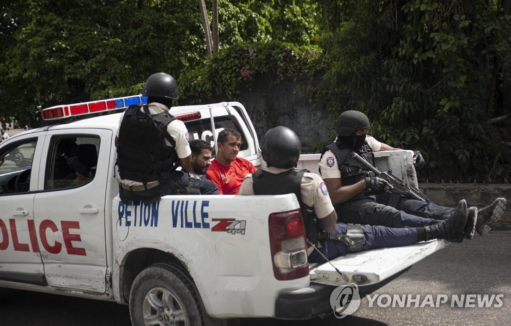 아이티 대통령 암살 용의자로 추정되는 남성 2명이 8일(현지시간) 경찰차로 이송되고 있다.