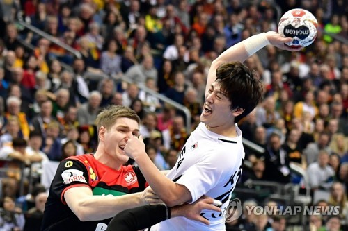 In this AFP photo, Kang Jeon-gu of Korea (R) takes a shot past Finn Lemke of Germany during their Group A match at the International Handball Federation World Men's Handball Championship at Mercedes-Benz Arena in Berlin on Jan. 10, 2019. (Yonhap)