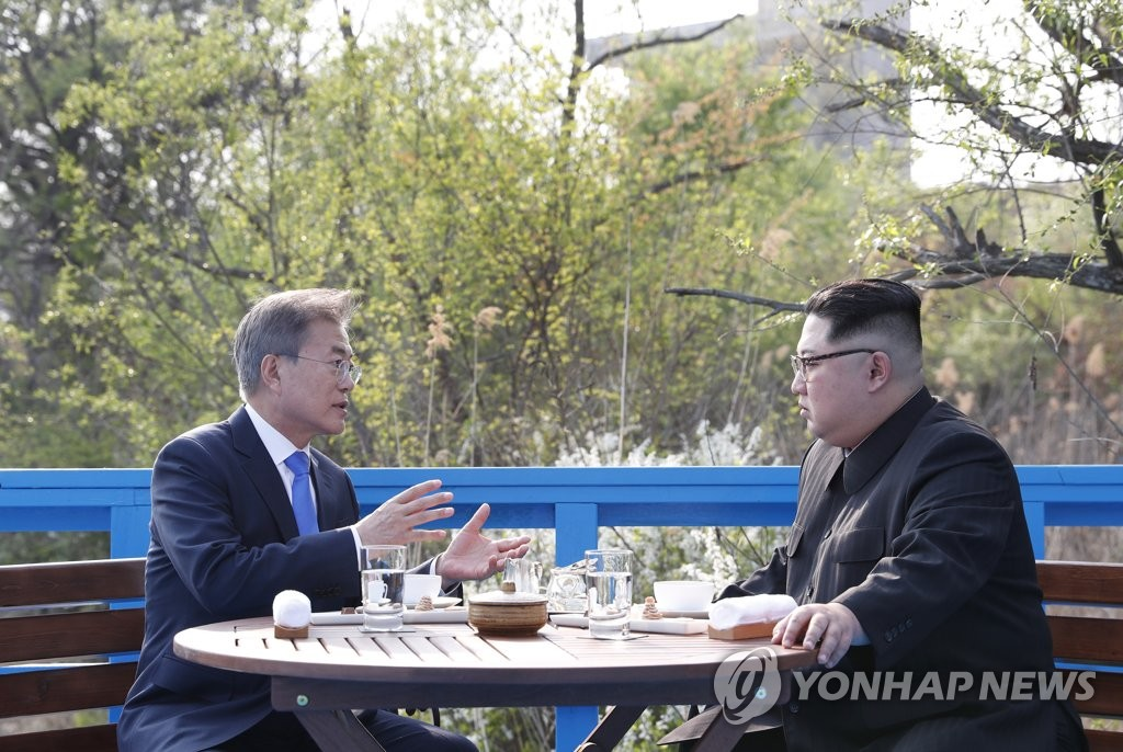 South Korean President Moon Jae-in (L) and North Korea's leader Kim Jong-un hold a private conversation during their summit at the truce village of Panmunjom on April 27, 2018. (Yonhap)
