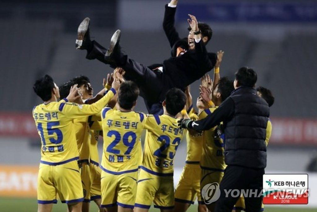 This photo taken by the K League on Nov. 5, 2018, shows Asan Mugunghwa head coach Park Dong-hyuk (C) being tossed in the air by his players after his side won the K League 2 title. (Yonhap)