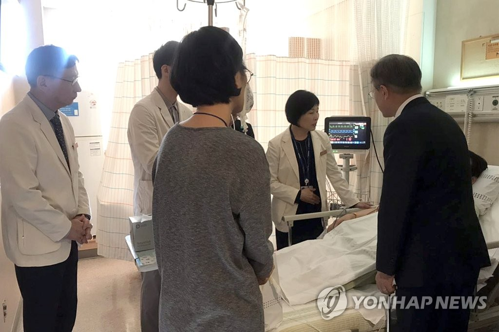In the photo provided by the presidential office Cheong Wa Dae, President Moon Jae-in (R) visits a finance ministry official who recently suffered a stroke while working late for the parliamentary passage of the government budget bill, at a Seoul hospital on Dec. 7, 2018. (Yonhap)