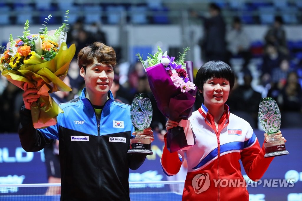 Jang Woo-jin of South Korea (L) and Cha Hyo-sim of North Korea hold up their second-place trophies in the mixed doubles during the awards ceremony at the International Table Tennis Federation World Tour Grand Finals on Dec. 15, 2018, at Namdong Gymnasium in Incheon, 40 kilometers west of Seoul. (Yonhap)
