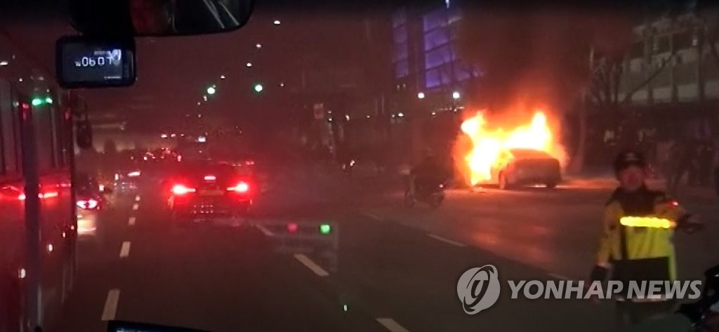 This photo, provided by Seoul's Jongno Fire Station near Gwanghwanun Station on Jan. 10, 2019, captures the taxi being engulfed in a blaze while firefighters are getting closer to the scene to put out the fire. (Yonhap)