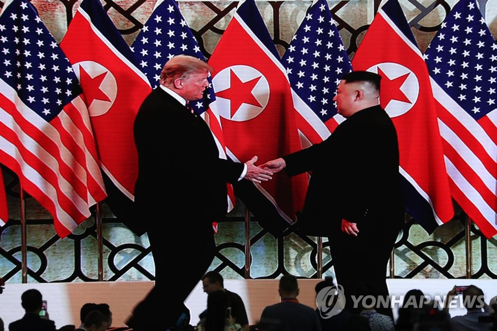 U.S. President Donald Trump (L) and North Korean leader Kim Jong-un shake hands before beginning their summit in Hanoi, Vietnam, on Feb. 27, 2019, in footage broadcast live to members of the domestic and international media at the International Media Center in the Vietnamese capital. (Yonhap)