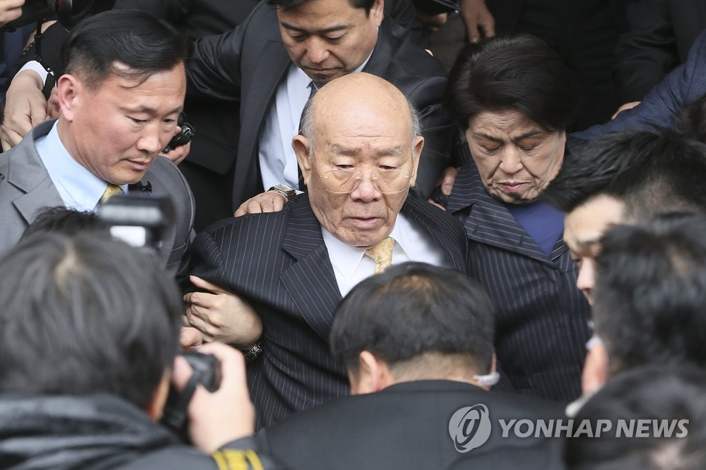 Escorted by bodyguards, former President Chun Doo-hwan moves toward his car after attending a hearing at a district court in the southwestern city of Gwangju on March 11, 2019. (Yonhap)