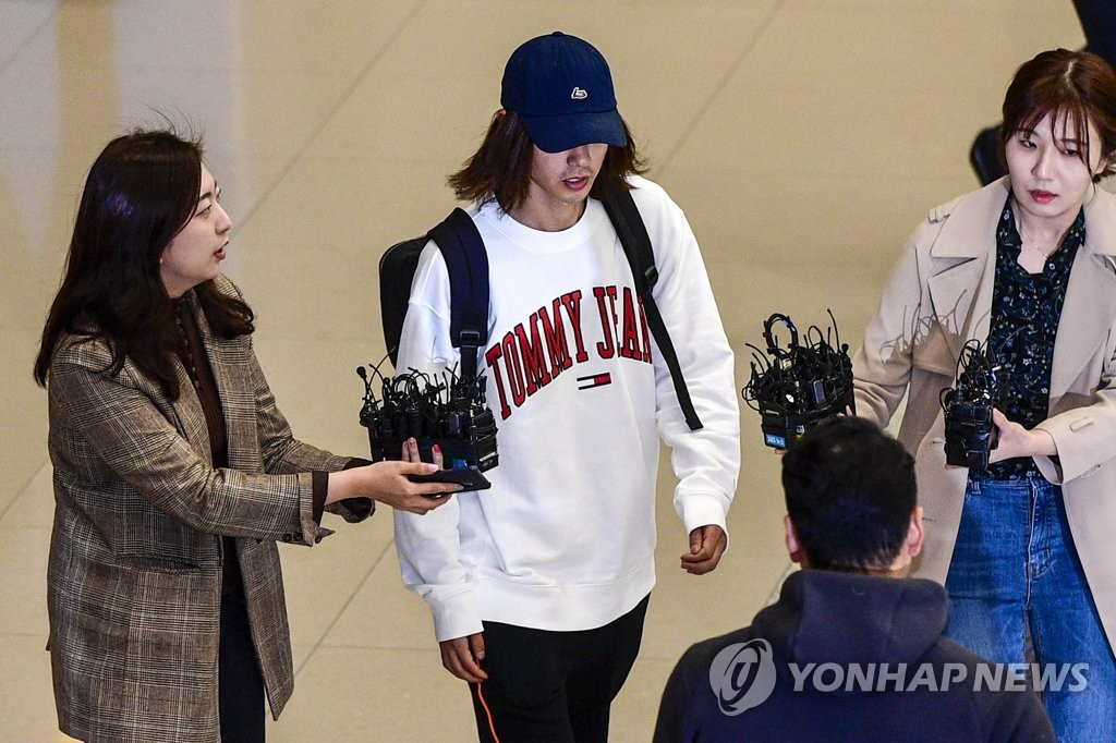 Jung Joon-young (C), a singer-songwriter and TV celebrity who is booked by police over illegal filming and leaking visual materials, is surrounded by reporters at Incheon International Airport in Incheon on March 12, 2019. (Yonhap)