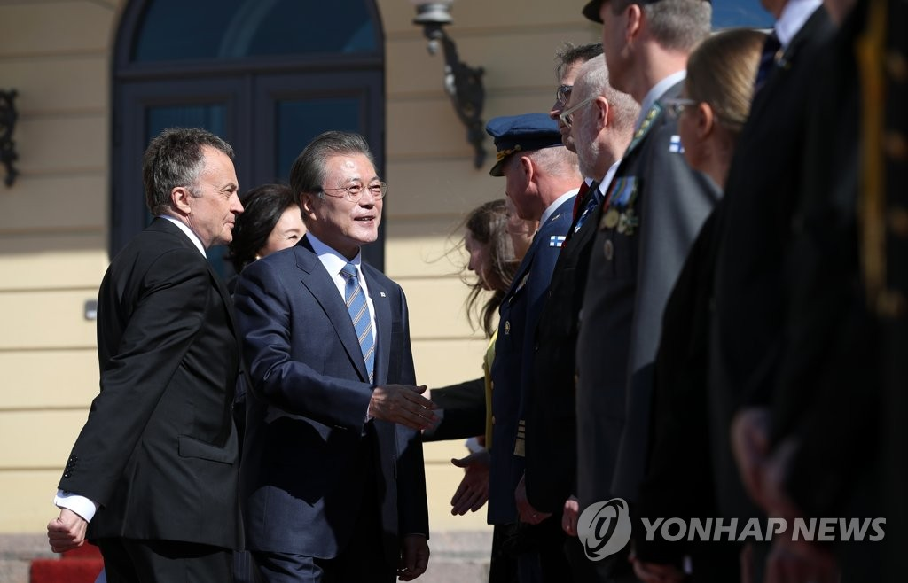 South Korean President Moon Jae-in shakes hands with a Finnish official during an official welcoming ceremony at the presidential place in Helsinki on June 10, 2019. (Yonhap)