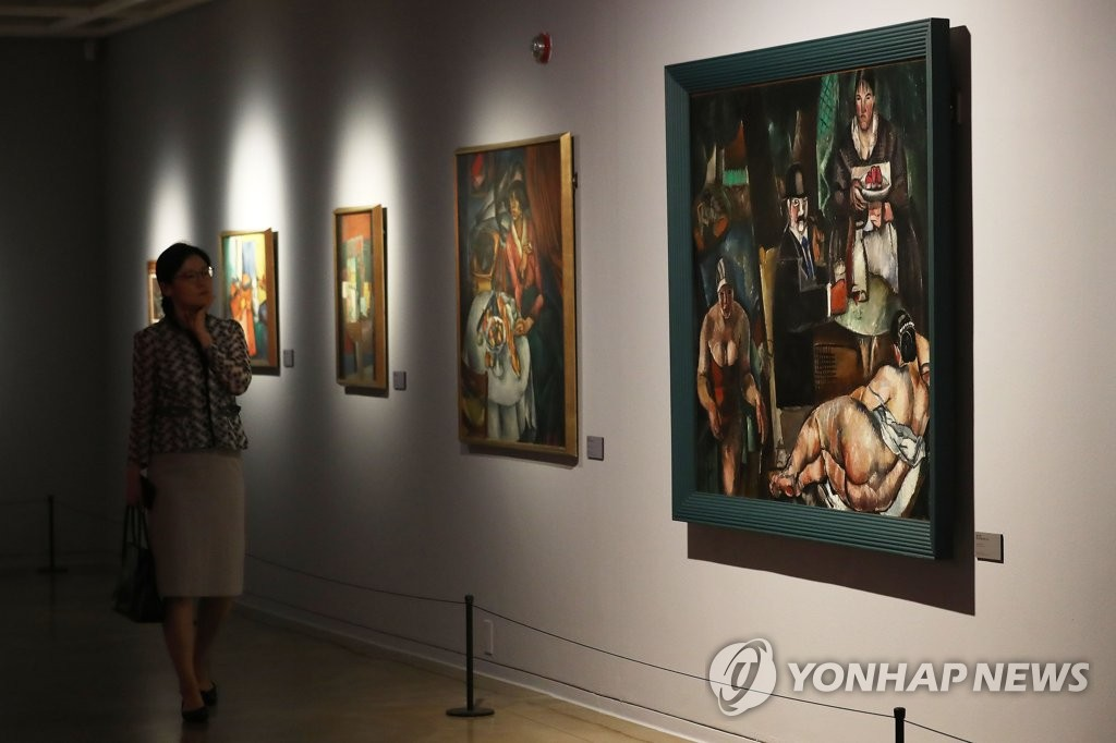 "Visitors look at paintings on display during an exhibition titled ""Revolution - The new era begins,"" which opened at Sejong Museum of Art in central Seoul on June 12, 2019. (Yonhap)"