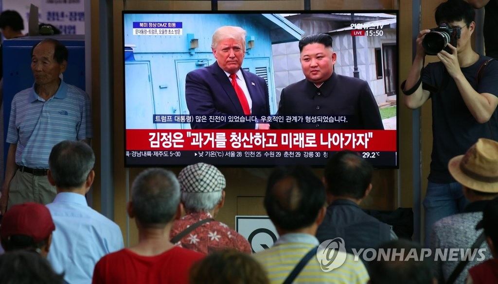 Seoul citizens watch U.S. President Donald Trump and North Korean leader Kim Jong-un shaking hands at the inter-Korean border on TV on June 30, 2019, in a waiting room at Seoul Station. (Yonhap)