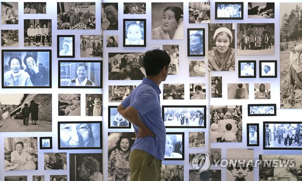 A visitor looks at photos of so-called comfort women at an exhibition at a Seoul gallery on Aug. 8, 2019. The event was arranged by the House of Sharing, a shelter for such women, and the gender equality ministry. As many as 200,000 women, mostly Koreans, were forcibly taken to front-line brothels for Japanese soldiers during World War II and were euphemistically called comfort women. (Yonhap)