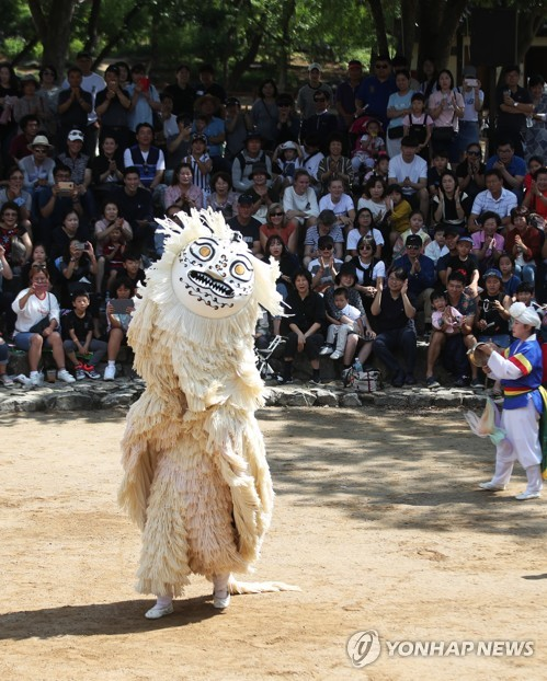 Spectators watch lion dance at folk village
