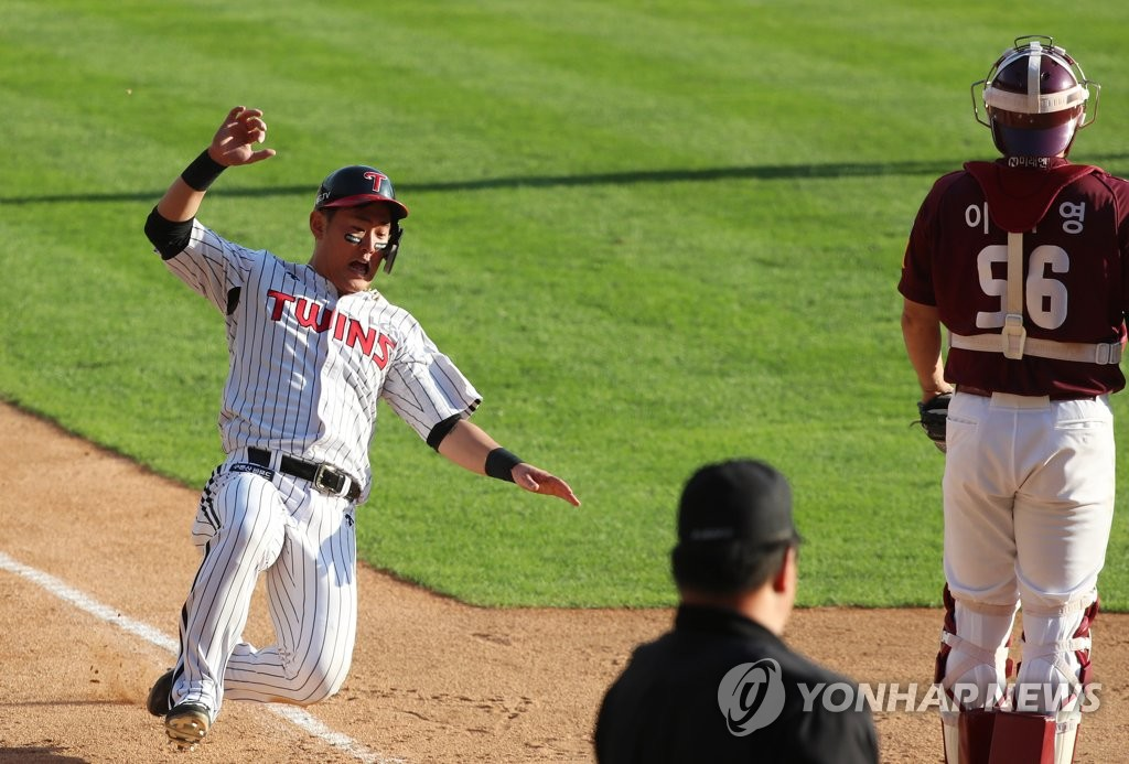 Jung Ju-hyeon of the LG Twins (L) slides home against the Kiwoom Heroes in the bottom of the seventh inning of Game 3 of their first-round playoff series in the Korea Baseball Organization at Jamsil Stadium in Seoul on Oct. 9, 2019. (Yonhap)