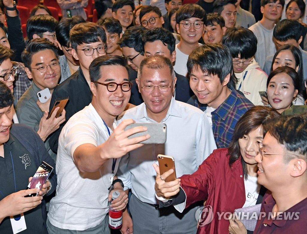 This photo taken on Oct. 22, 2019, and provided by Hyundai Motor Group shows the group's executive vice chairman, Chung Euisun (C), and employees taking selfies with the carmaker's heir apparent after a town hall meeting at its headquarters in Yangjae, southern Seoul. (PHOTO NOT FOR SALE)(Yonhap)