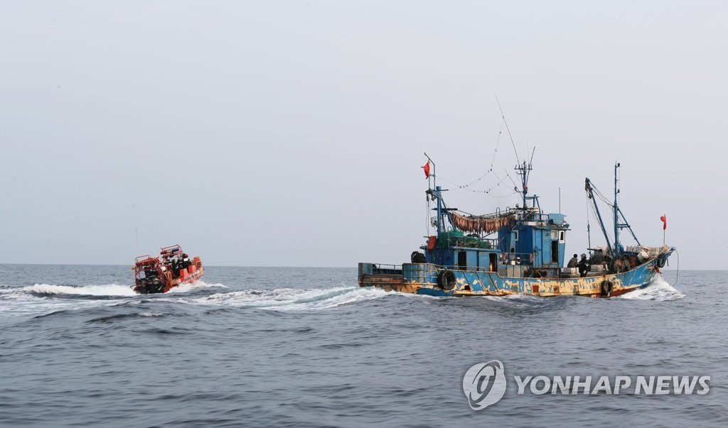 A Coast Guard motor boat (L) approaches a Chinese fishing boat operating without permission in South Korea's exclusive economic zone on Oct. 25, 2019. (PHOTO NOT FOR SALE) (Yonhap)
