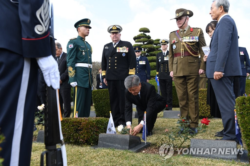 South Korea's veterans affairs minister Park Sam-Duck (C) lays flower on the grave of James Patrick Daunt of Australia. A ceremony to commemorate international participation in the 1950-53 Korean war was held at the U.N. Memorial Cemetery in South Korea's southern port city of Busan on Nov. 11, 2019 (Yonhap)