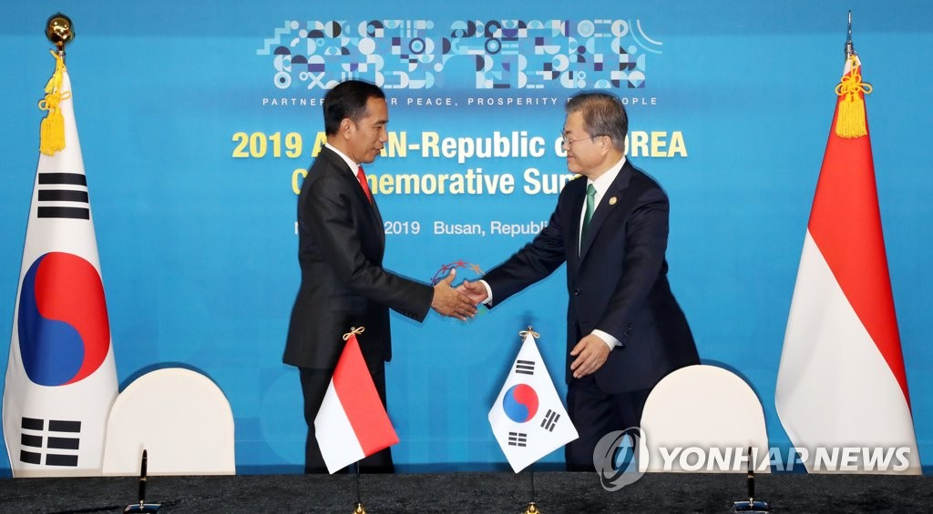 South Korea's President Moon Jae-in (R) and Indonesia's President Joko Widodo shake hands during their meeting on the sidelines of a special summit between South Korea and the Association of Southeast Asian Nations (ASEAN) in the port city of Busan, 450 kilometers southeast of Seoul, on Nov. 25, 2019. (Yonhap)