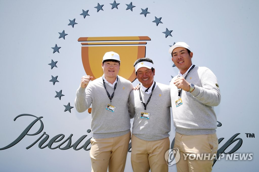 In this photo provided by the Korea PGA, South Korean participants of the Presidents Cup pose for a photo in front of the competition's logo at Royal Melbourne Golf Club in Melbourne on Dec. 10, 2019. From left, player Im Sung-jae, assistant captain Choi Kyoung-ju and player An Byeong-hun. (PHOTO NOT FOR SALE) (Yonhap)