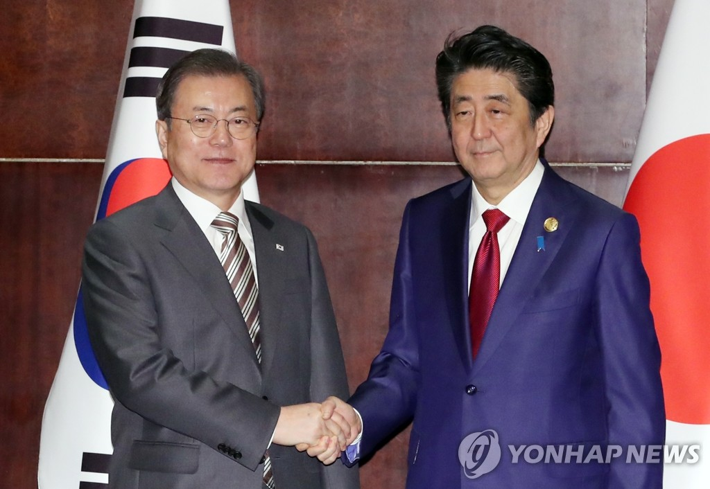 South Korean President Moon Jae-in (L) shakes hands with Japanese Prime Minister Shinzo Abe in Chengdu, China, on Dec. 24, 2019. (Yonhap)