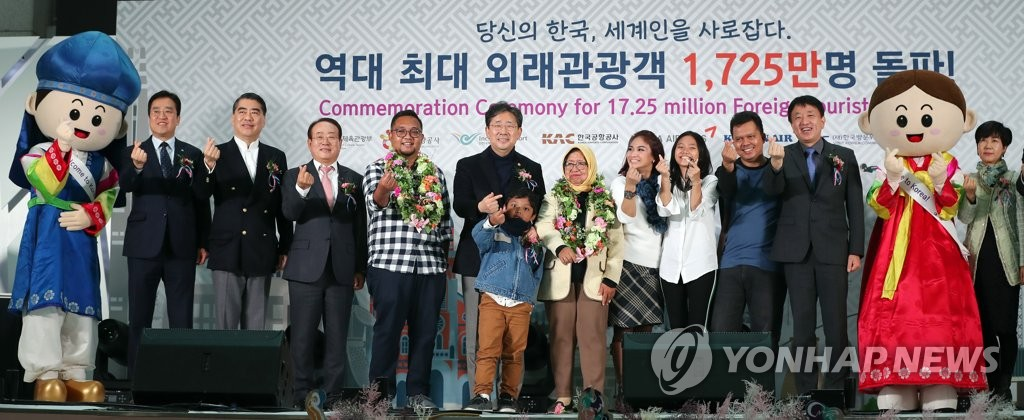 Minister of Culture, Sports and Tourism Park Yang-woo (6th from L) celebrates the arrival of this year's 17.25 millionth foreign visitor to South Korea, Eko Prasetio (5th from L), and his family at Incheon International Airport, west of Seoul, on Dec. 26, 2019, in this photo provided by Park's ministry. (PHOTO NOT FOR SALE) (Yonhap)