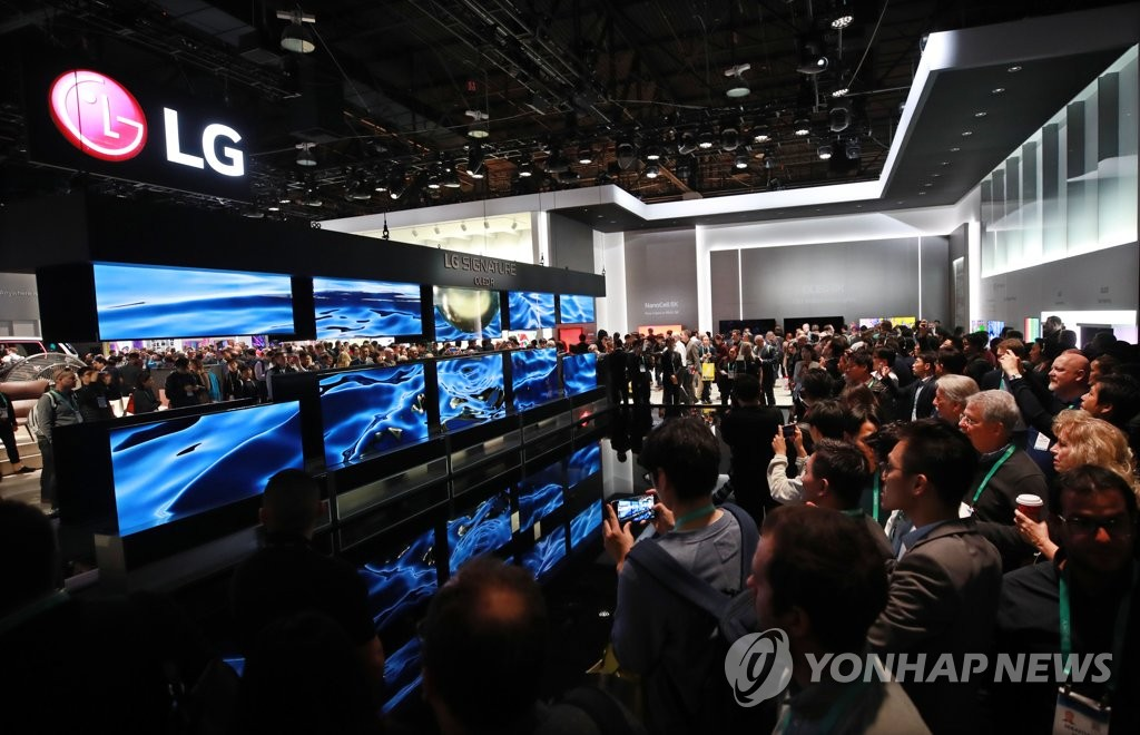 Visitors at the Consumer Electronics Show (CES) take photos of LG Electronics Inc.'s rollable TVs at the company's CES booth in Las Vegas, Nevada, on Jan. 8, 2020. (Yonhap)