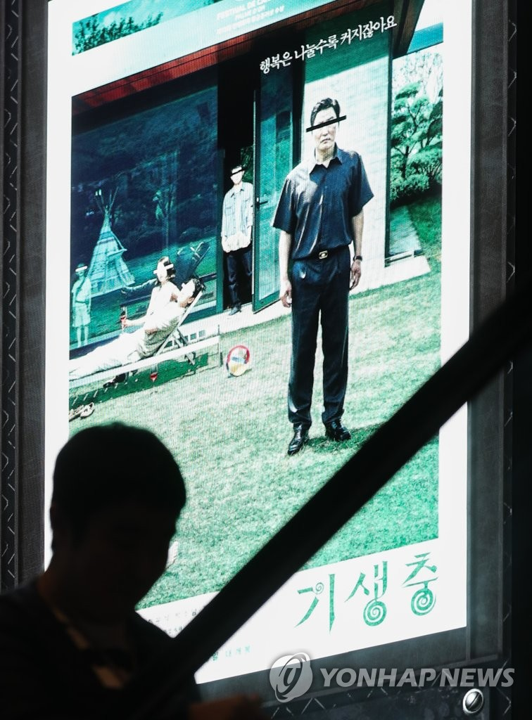 "In the Feb. 11, 2020, file photo, a poster of ""Parasite"" is shown on an electronic board at a CGV theater in Seoul, as CJ CGV, South Korea's largest multiplex cinema chain, decided to rerelease the Oscar-winning film until Feb. 25 at 32 of its theaters nationwide, including 13 in Seoul. (Yonhap)"