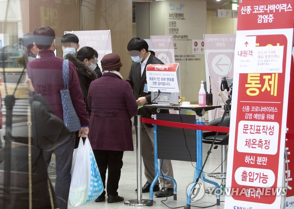 Officials at Seoul National University Hospital in Seoul, where South Korea's 29th coronavirus patient has been hospitalized, check visitors for fever to prevent the spread of the coronavirus on Feb. 16, 2020. (Yonhap)